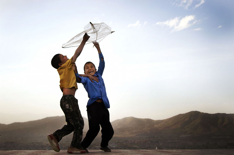 Afghan boys play with their kite on a hill overlooking Kabul, Afghanistan, Monday, May 13, 2013. Banned during the Taliban regime, kite flying is once again the main recreational escape for Afghan boys and some men. (AP Photo/Anja Niedringhaus)