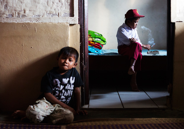 Ilham Hadi, who has smoked up to two packs a day and began when he was four years old, poses for a photo wearing his third grade uniform while smoking in his bedroom as he younger brother looks on February 14, 2014. (Photo By: Michelle Siu)