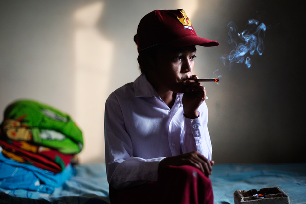 Ilham Hadi, who has smoked up to two packs a day and began when he was four years old, poses for a photo wearing his third grade uniform while smoking in his bedroom on February 14, 2014. (Photo By: Michelle Siu)