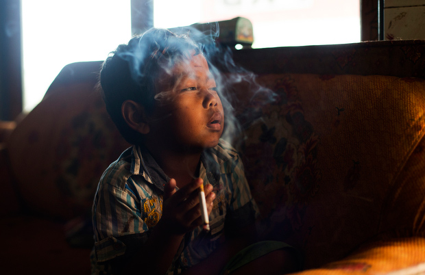 Dihan Muhamad, who used to smoke up to two packs of cigarettes a day before cutting down, poses for a photo as he smokes in his home on February 10, 2014. (Photo By: Michelle Siu)