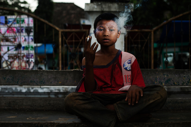 Cecep poses for a photo as he smokes on February 10, 2014. He is currently sleeping at a mosque and singing in buses to make money. (Photo By: Michelle Siu)