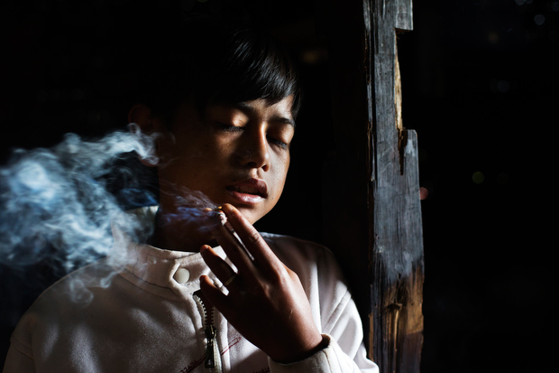 Illham Muhamad, who has smoked since he was five years old, poses for a photo as he slowly inhales his first cigarette of the day at his grandmother's home on February 10, 2014. He does not attend school and if his grandmother refuses to give him money to buy cigarettes he will go through withdrawal and cry and throw fits. (Photo By: Michelle Siu)