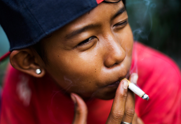 "Ompong, which means ""toothless"" in the local language of Bahasa, poses for a photograph as he has a cigarette on February 14, 2014.  (Photo By: Michelle Siu)"