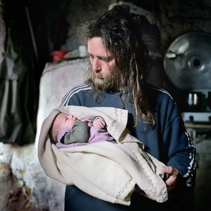 Angelo takes care of the newborn Siria in the kitchen of the old house.