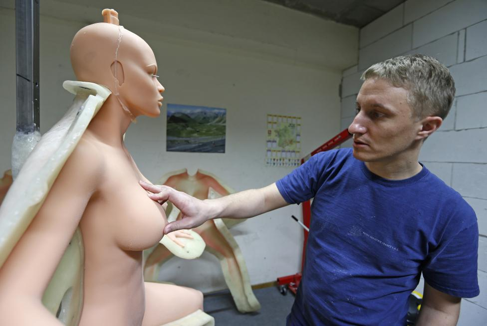 Eric, an employee at the Dreamdoll company, inspects a silicone dream doll as he removes it from a mold at their workshop in Duppigheim near Strasbourg, December 2, 2014. REUTERS/Vincent Kessler