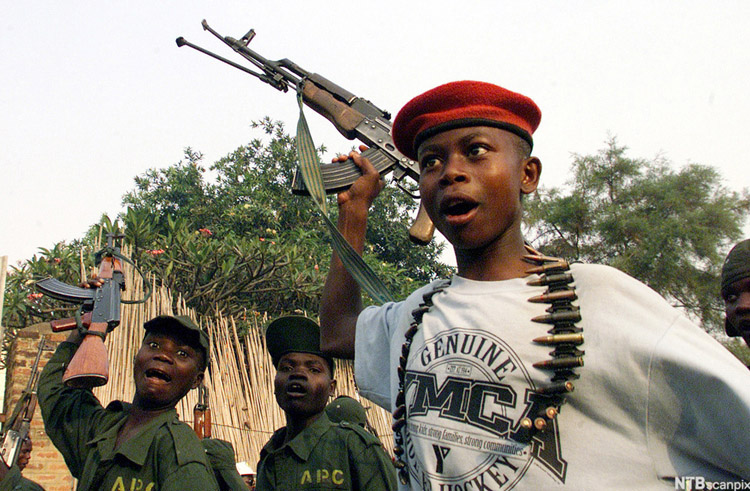 Young soldiers from a Ugandan supported Congolese rebel movement group, sing liberation songs waving their rifles in this Jan. 30, 2002 photo in the north eastern Congolese town of Bunia. For decades, boys have been a mainstay of rebel armies around the world, the United Nations estimates that more than 300,000 children under the age of 18 are currently fighting worldwide, mostly with rebel groups. (AP Photo/Karel Prinsloo)