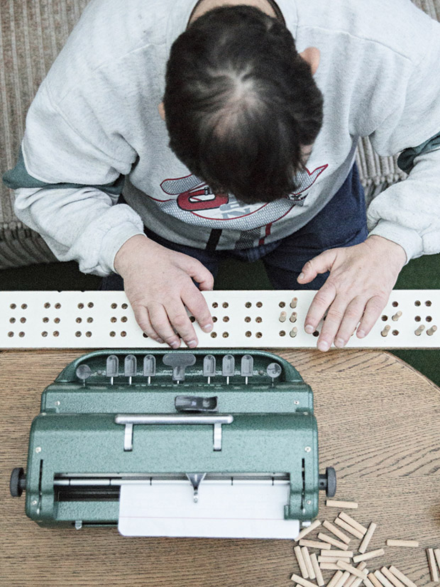 Jörg practices to type on a braille typewriter. His parents made him a wooden board where they put small wooden pins so Jörg can feel the letters.