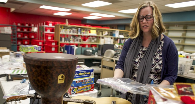 Lori Easterwood looks over a collection of board games and musical instruments at the Central Library in downtown Sacramento. After they are cataloged they will be sent to the Arcade Branch Library and made available to the public to check out. Andrew Nixon / Capital Public Radio